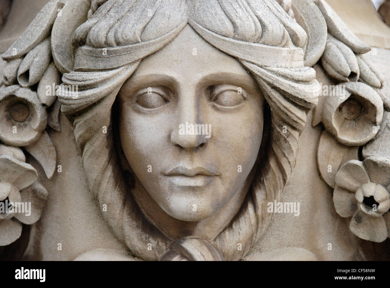 A carving of woman s face on stone urn in the italian