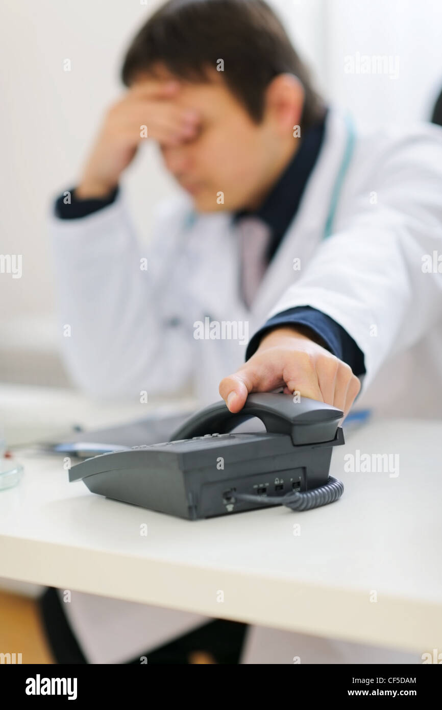 Frustrated office worker on the phone holding stock photo image - Frustrated Medical Doctor Picking Up Phone Handset Stock Image