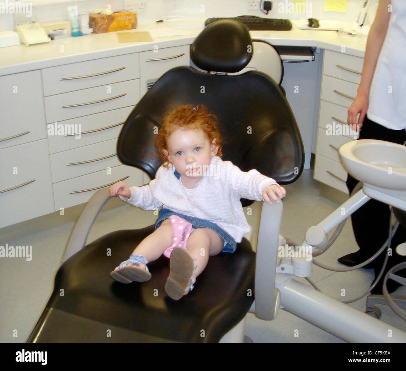 Black child sitting in chair - Female Child Curly Red Hair Wearing A Denim Dress And White Cardigan Sitting In Black Dentists Chair Unsmiling Looking At