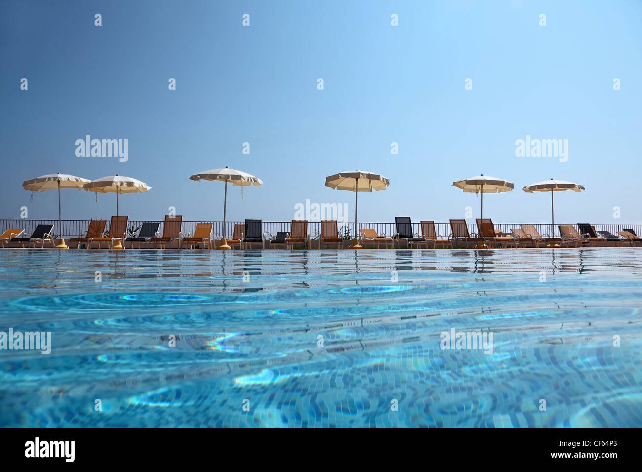 On Edge Of Pool Near Fence Deck Chairs Stand With Opened Beach Umbrellas,  Underwater Package Shot