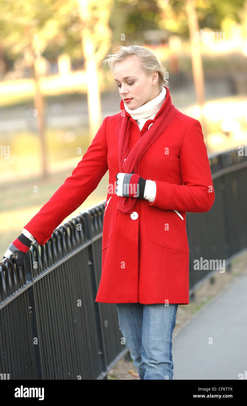 Female long blonde hair off face wearing cream poloneck red coat ...