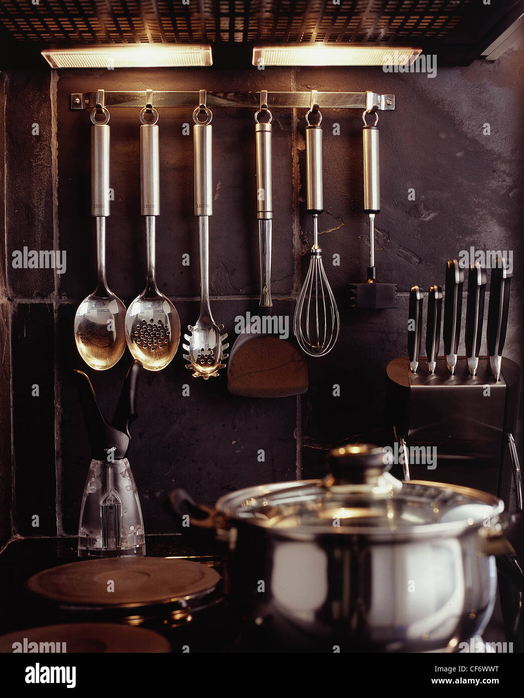 Hanging utensil rack for kitchen - Stock Photo B Three Different Kitchen Styles Rack Metal Kitchen Utensils Hanging From It On Back Rough Slate Tiled Wall Above Hob Saucepan
