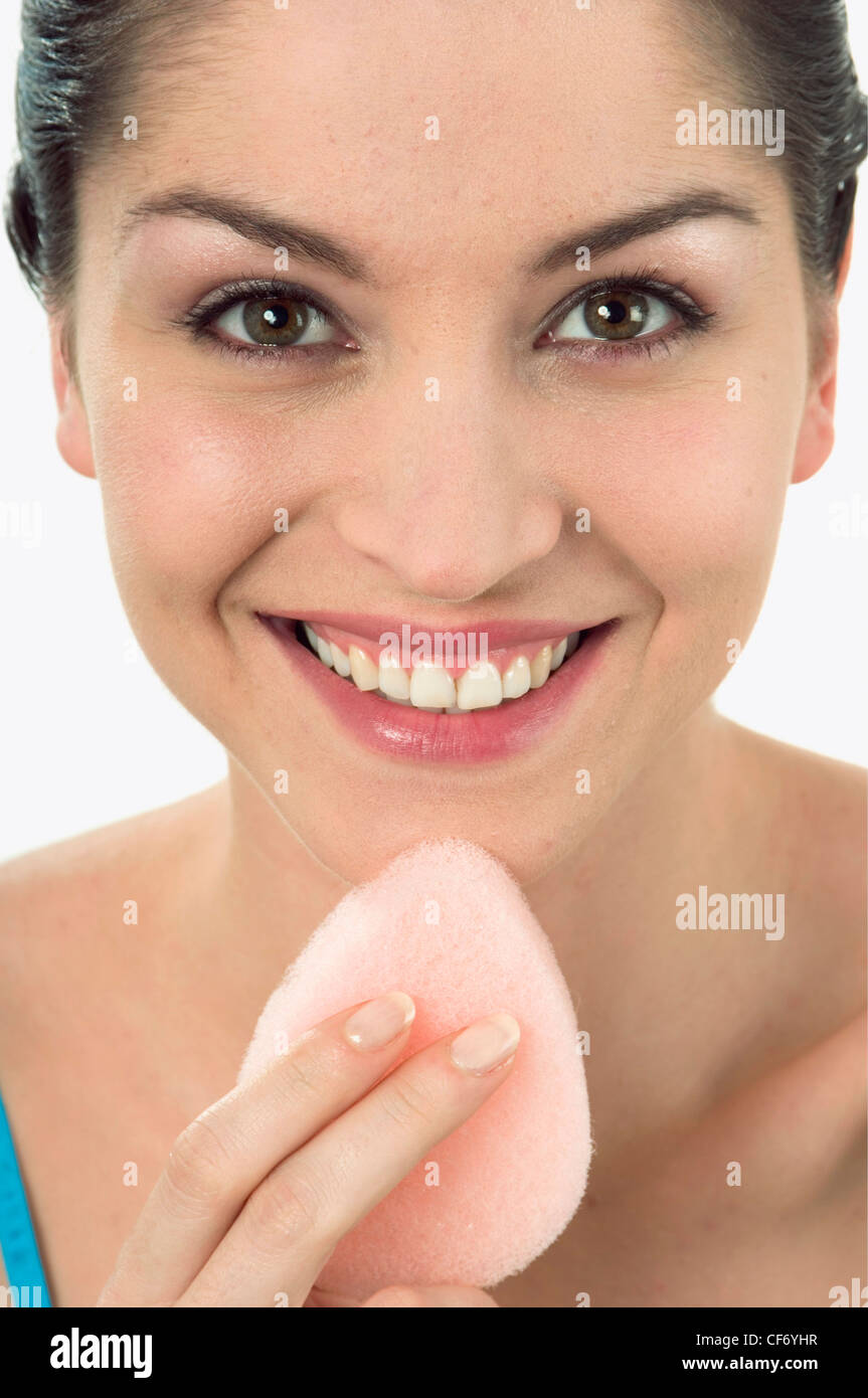 Female With Brunette Hair Off Face Using Pink Sponge To Exfoliate Chin  Looking To Camera Smiling
