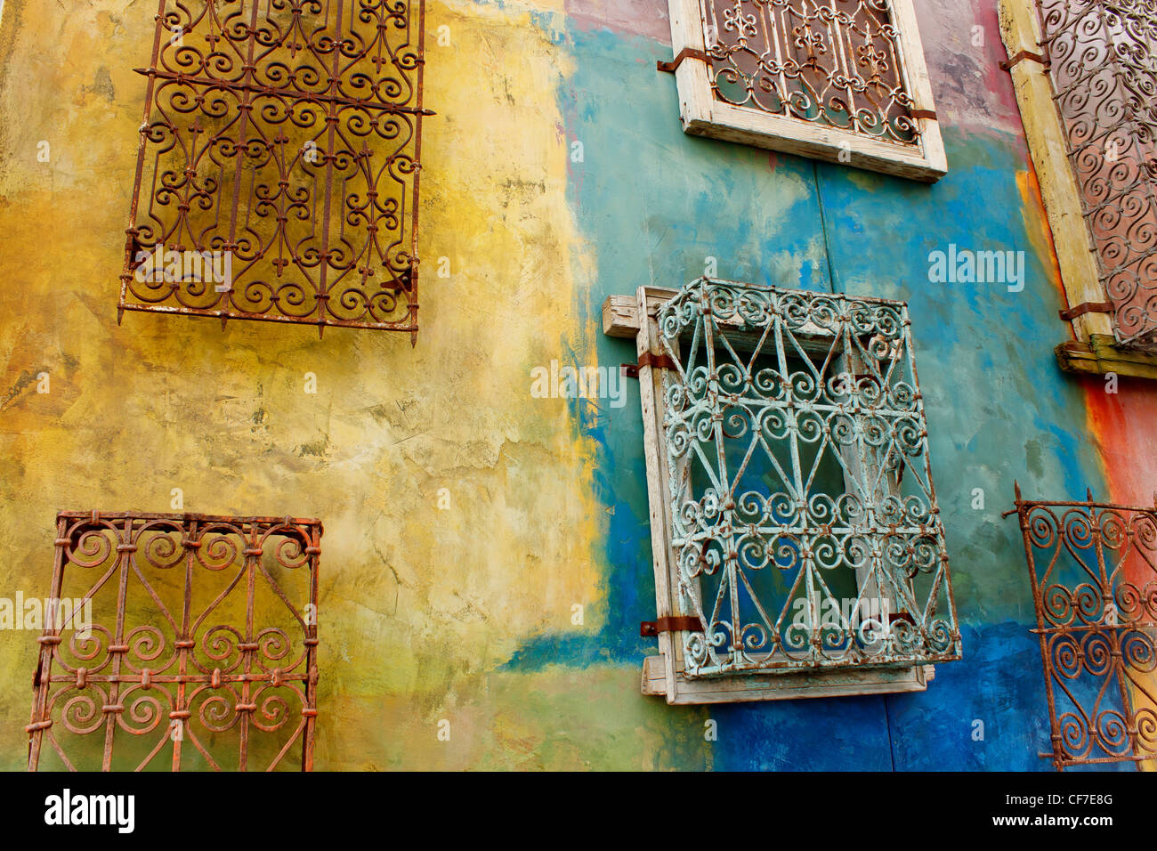 Colorful wall with wrought iron window covers in upscale ...
