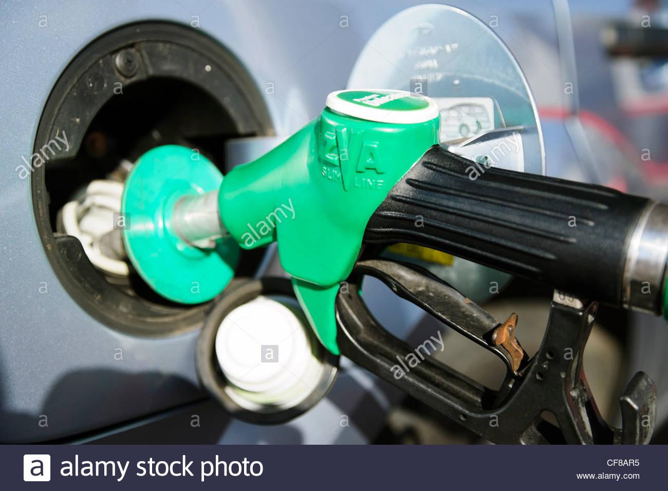 Close up of a petrol pump nozzle filling a car gas tank with unleaded fuel uk