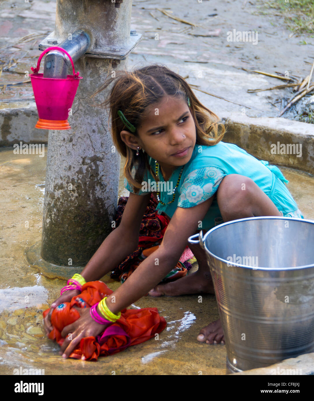 a young girl washing clothes at the village hand pump ...