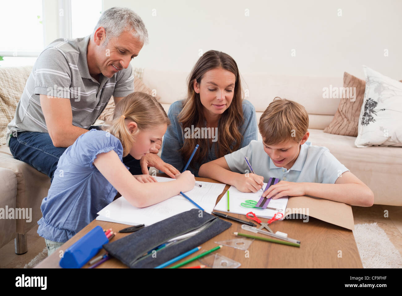 Parents Helping Their Children To Do Their Homework Stock Photo     Alamy Parents helping their children to do their homework