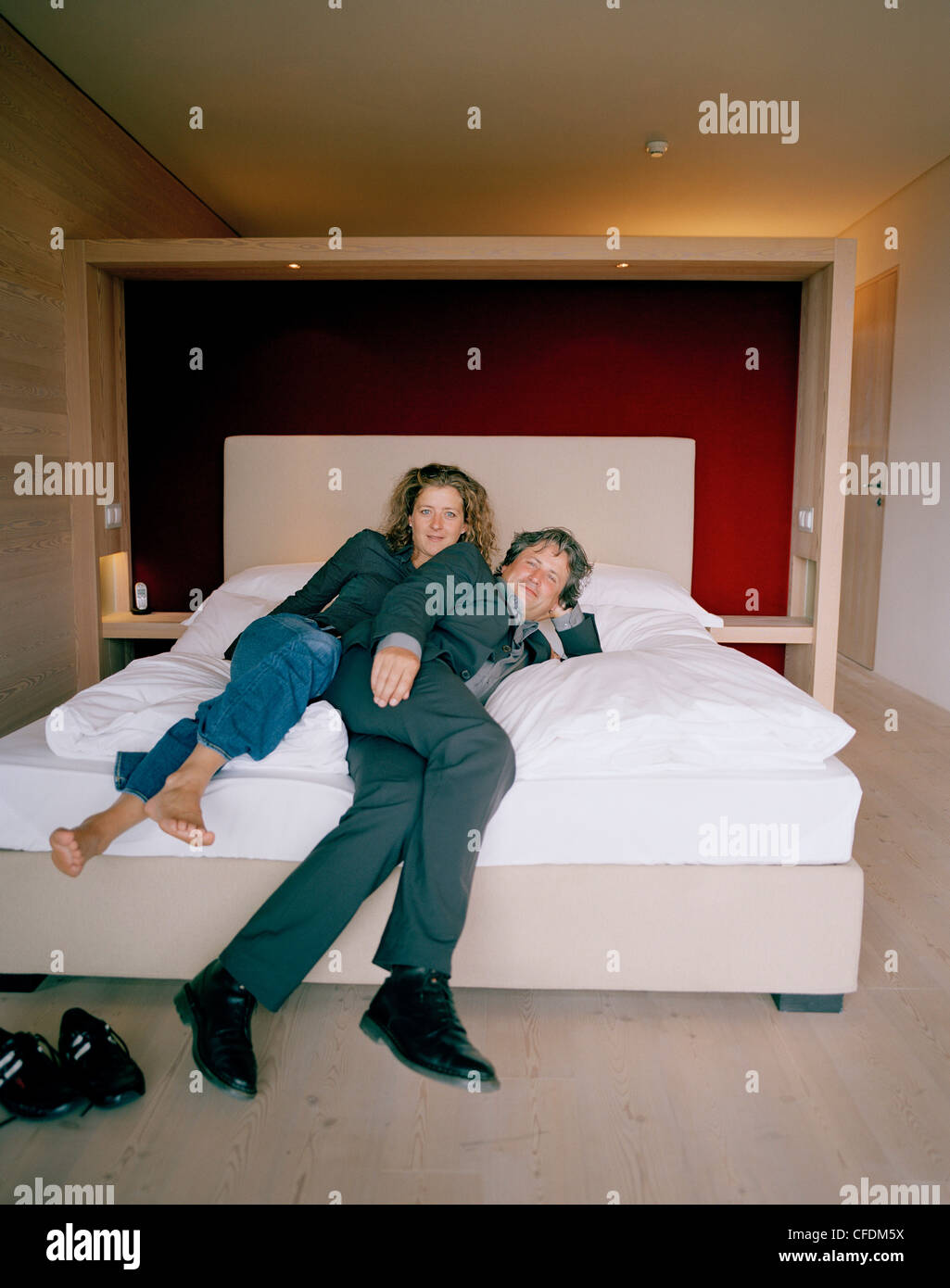 Couple on a bed in a hotel room vigilius mountain resort for Hotel in lana sudtirol
