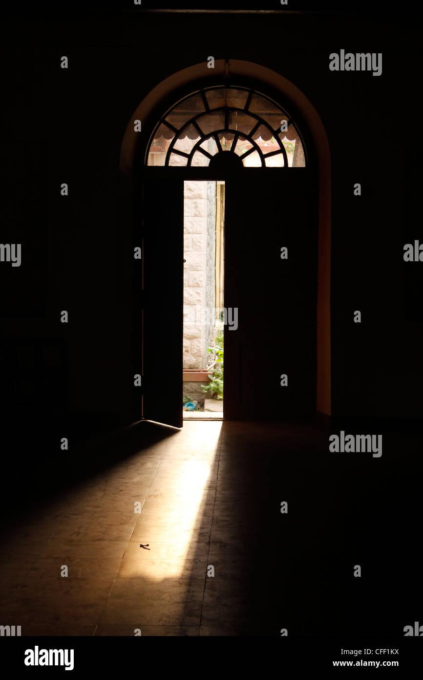 Dark room with light through door - Light Coming Through An Open Door Maharaja S College Ernakulam India Stock Photo