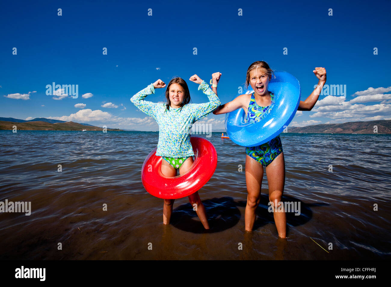 Two middle school aged sisters in bathing suites stand on the ...