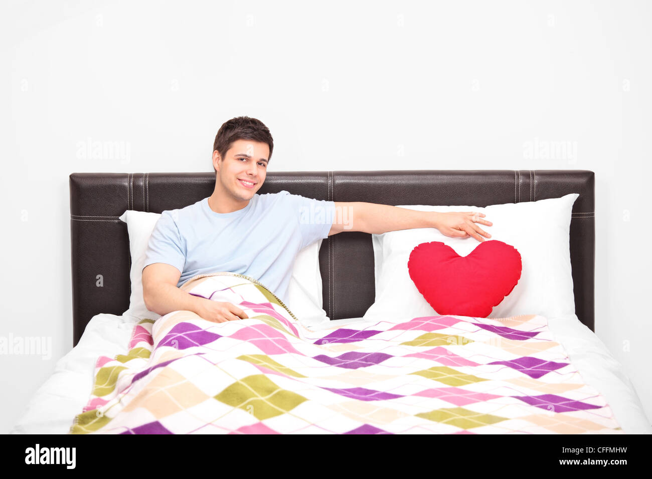 Man Shaped Pillow Young Man Resting On A Bed And A Heart Shaped Pillow Stock Photo