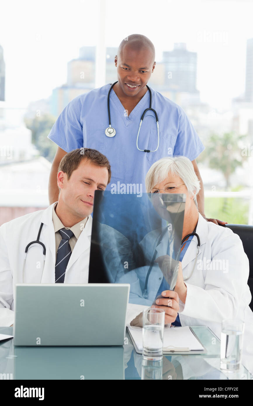 mature doctor explains an x-ray to colleagues stock photo, royalty