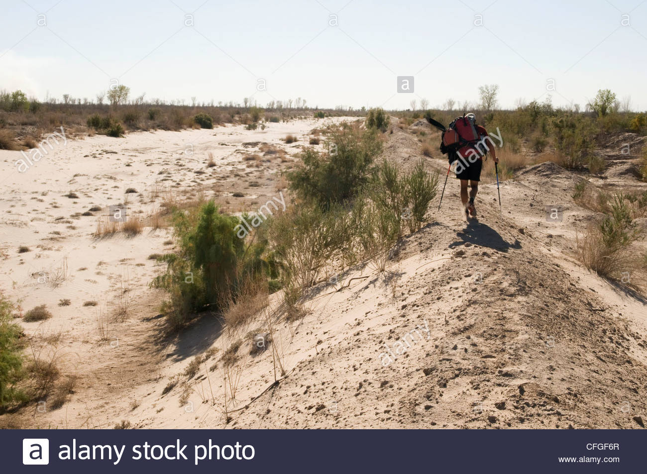 A man walks with a packraft across the dry Colorado River ...