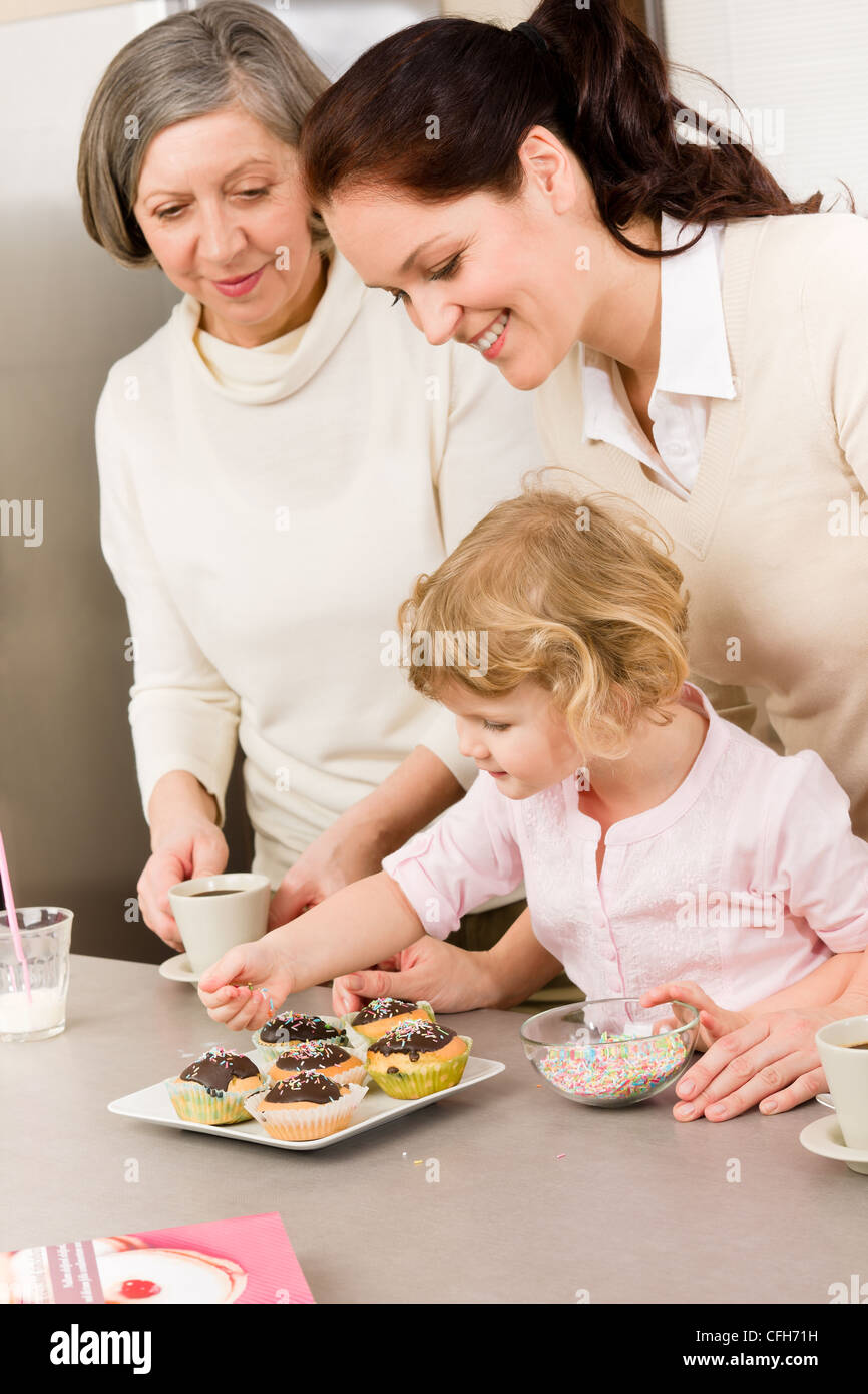 mother and daughter decorating cupcakes sprinkles happy together