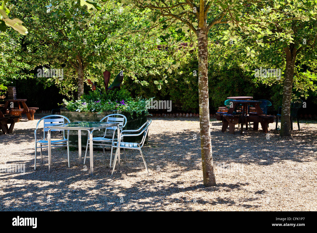 Cafe tables in dappled shade of trees on gravel patio in for Meaning of terrace in english