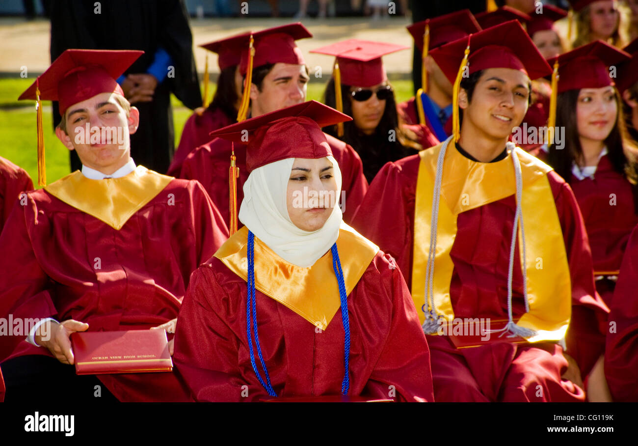 Wearing caps and gowns, high school seniors participate in ...