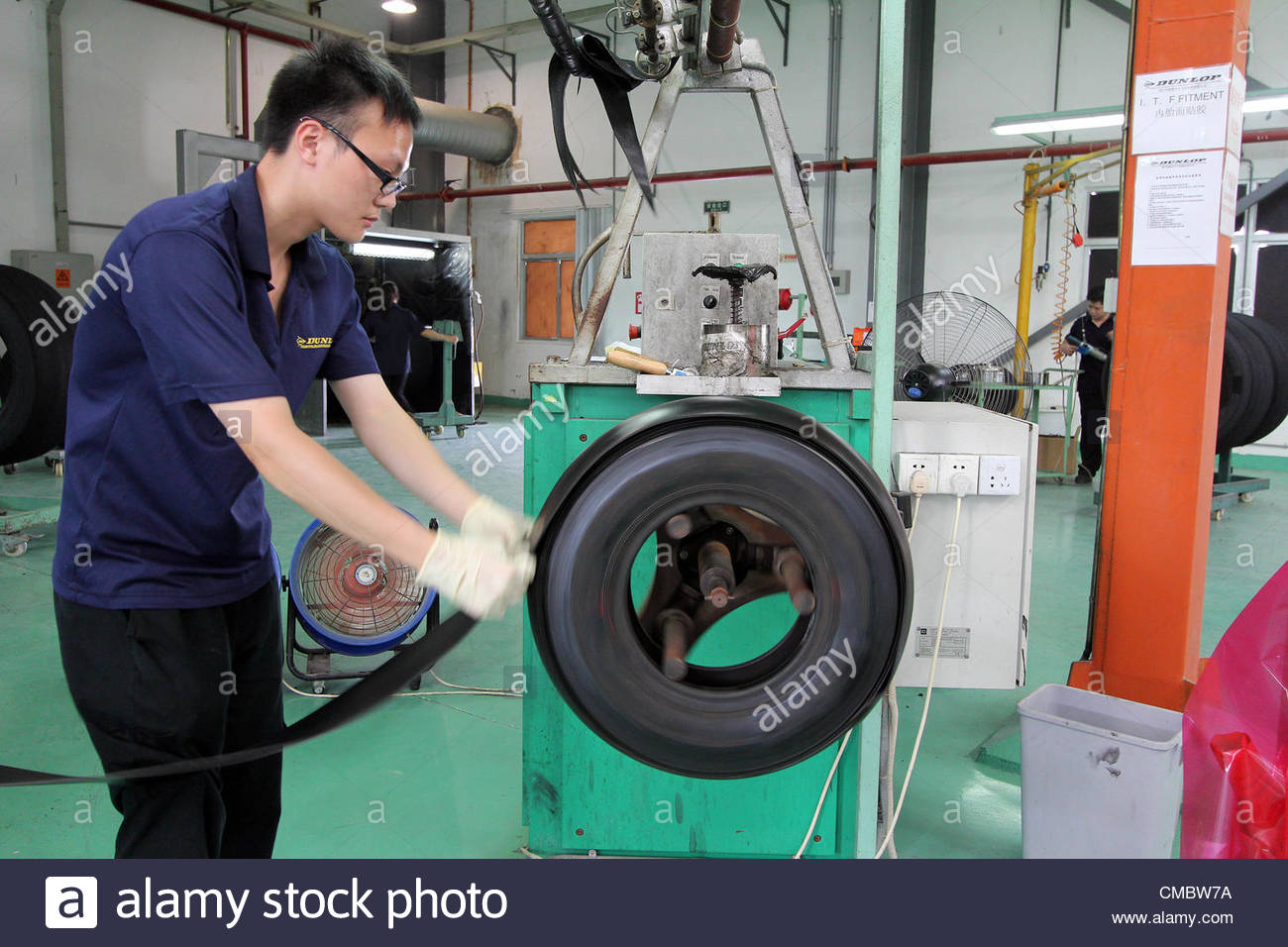 The workers are repairing airplane tyres at the factory of Dunlop ...