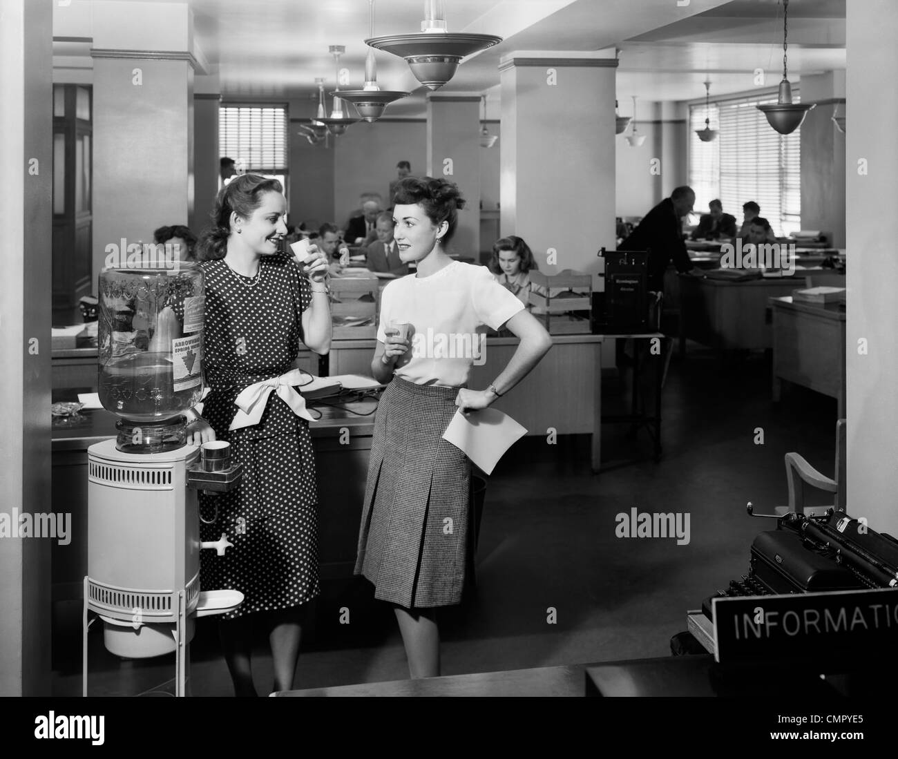 Office workers talking by water cooler in hallway Stock Photo ...