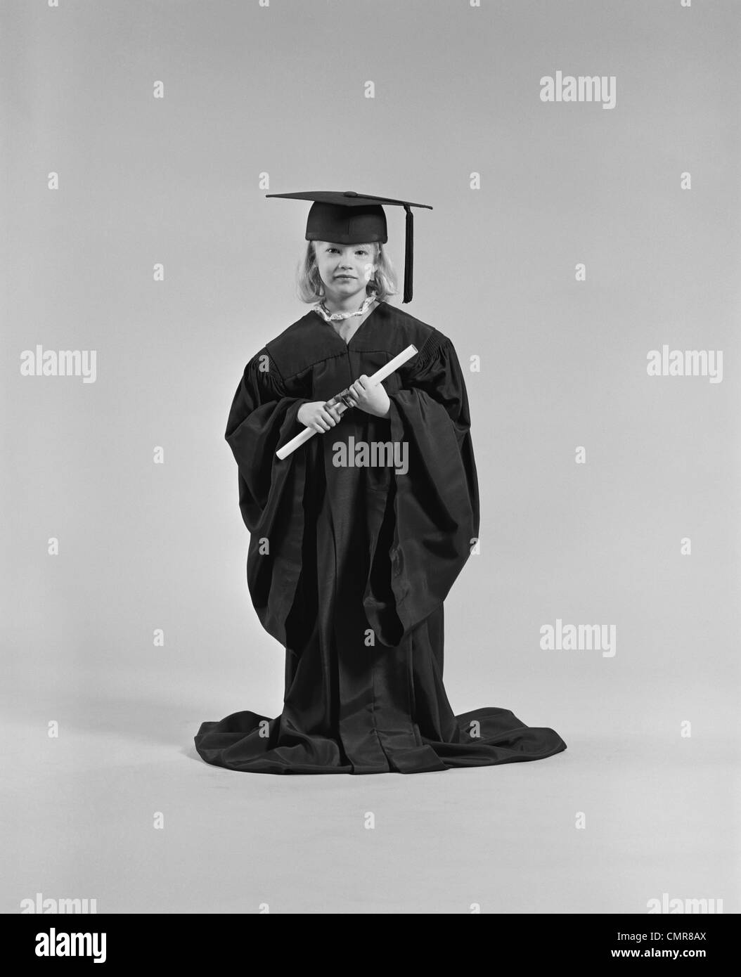 Black dress under white graduation gown - 1970s Girl Wearing Graduation Cap Gown Holding Diploma Stock Image