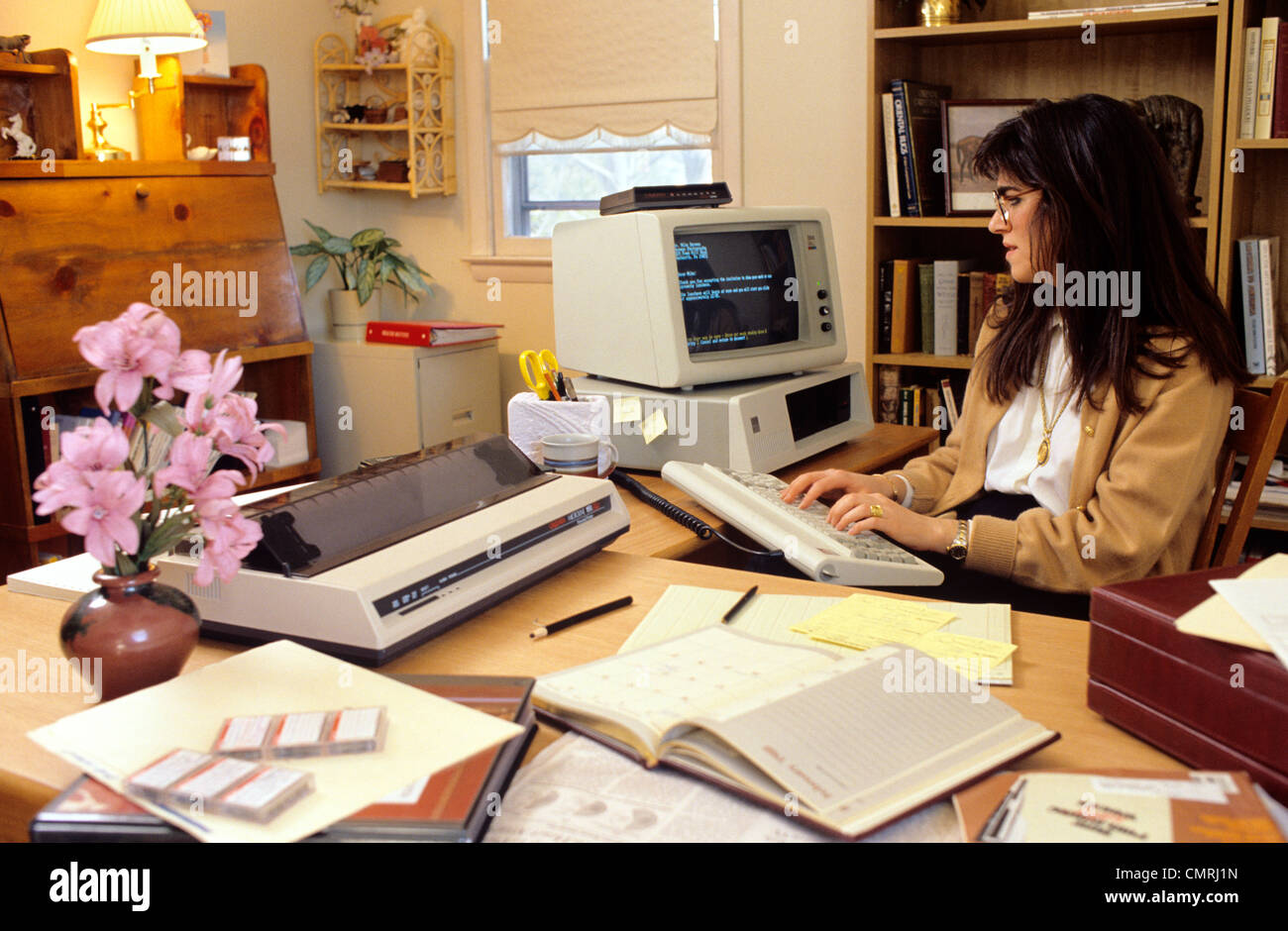 1980s 1990s freelance woman working on early ibm pc on desk in her home office home office early