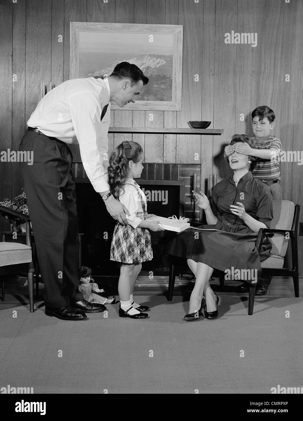 Living Room 1950s 1950s family living room woman mother getting surprise gift from