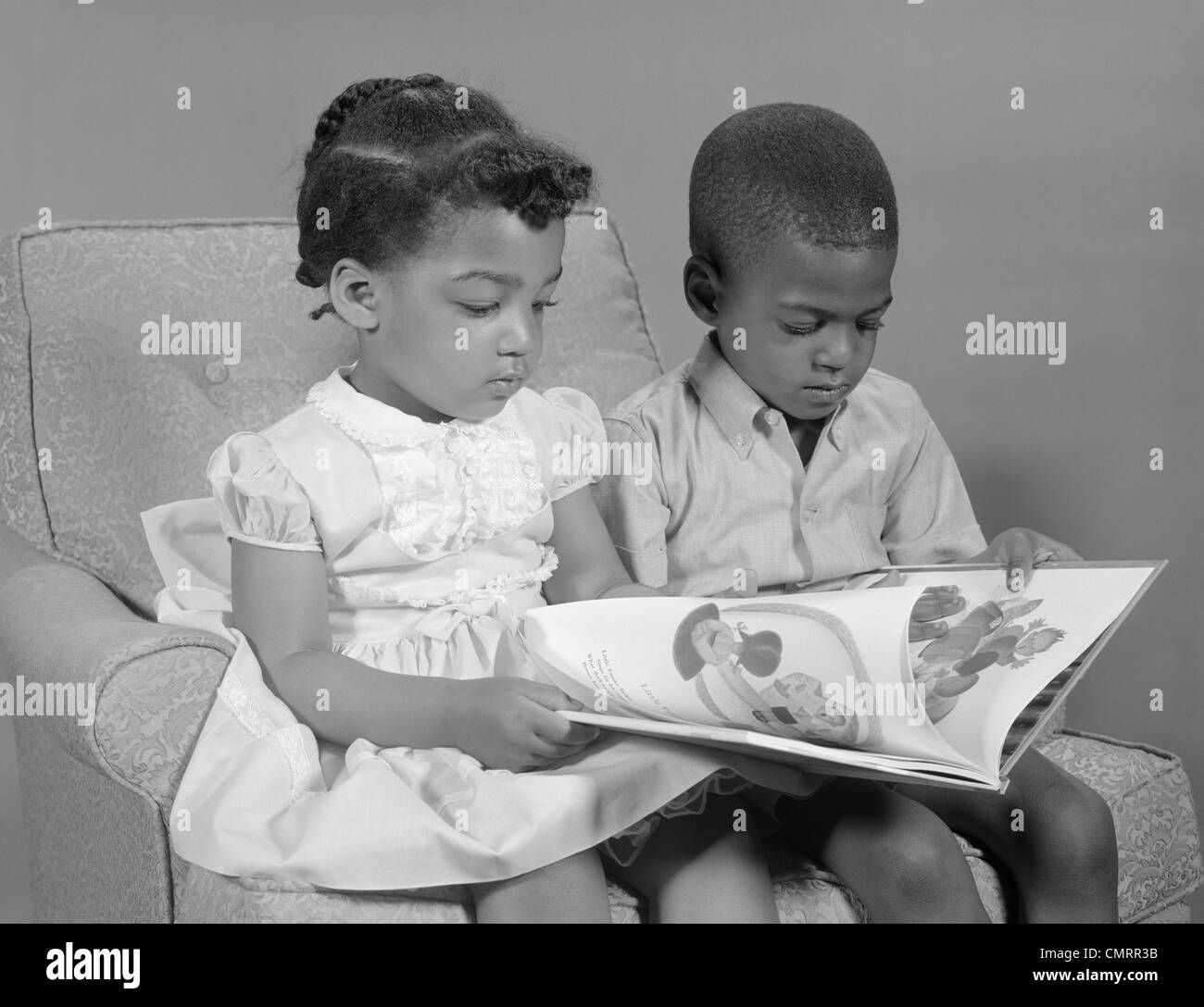 Black child sitting in chair - 1960s African American Boy And Girl Reading Book Sitting Chair