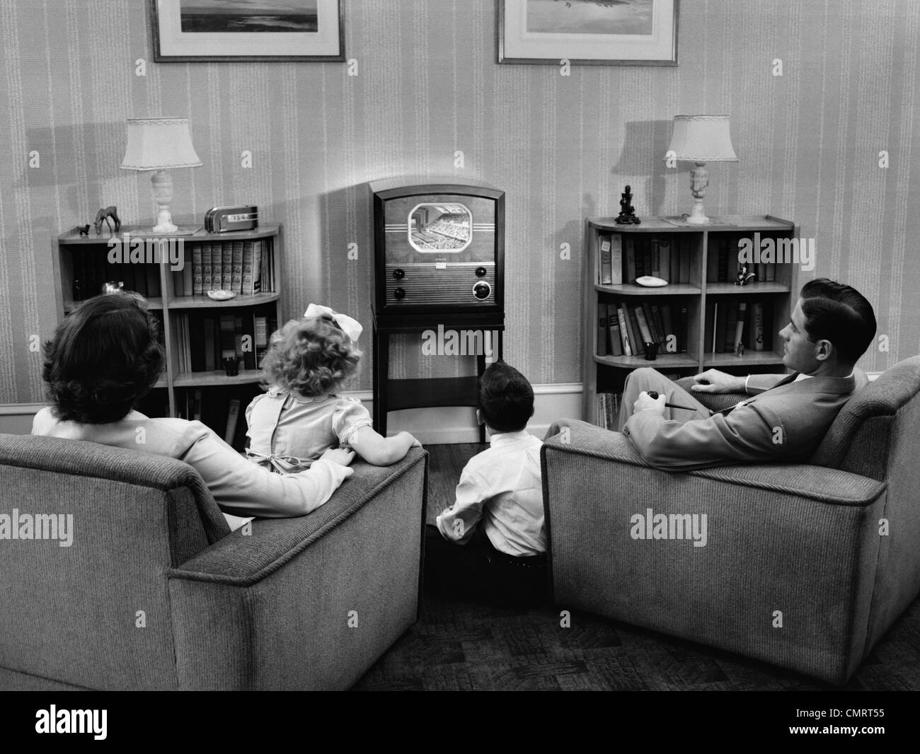 Living Room 1950s 1950s family in living room watching television stock photo