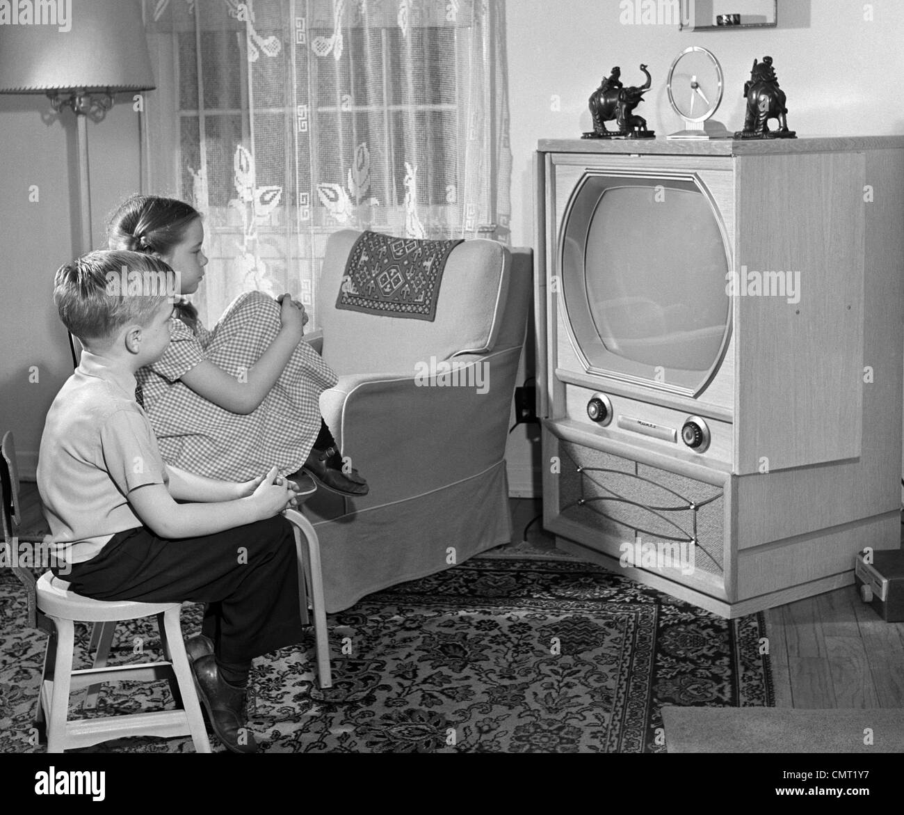 Living Room 1950s 1950s boy and girl watching tv in living room stock photo, royalty