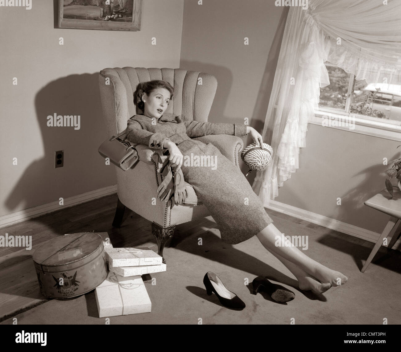 1950s Exhausted Female Slumped In Chair With Shoes Off