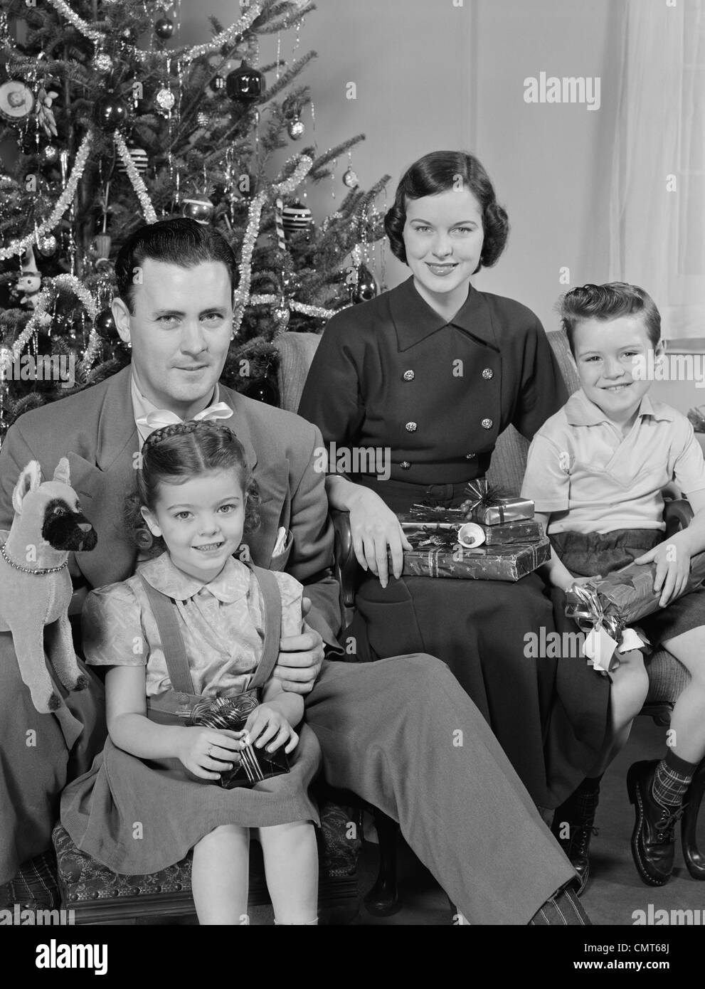 1950s FAMILY PORTRAIT BY CHRISTMAS TREE LOOKING AT CAMERA ...