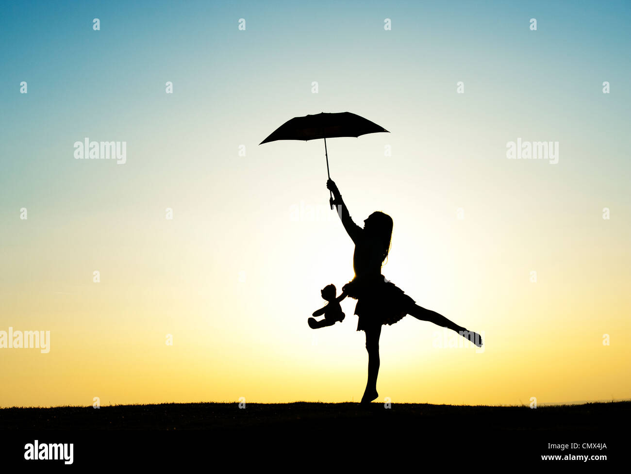 young jumping with an umbrella and teddy bear at sunset stock