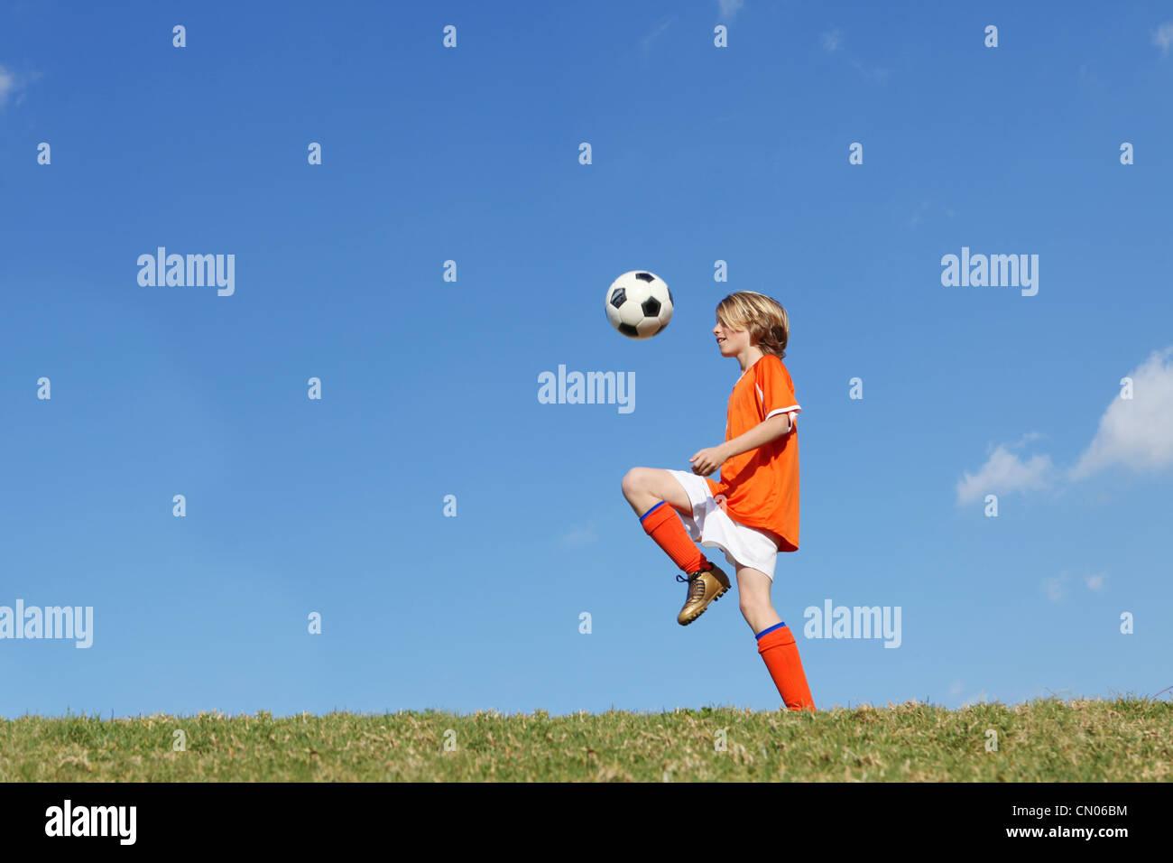 boy kid playing soccer kicking football stock photo royalty free