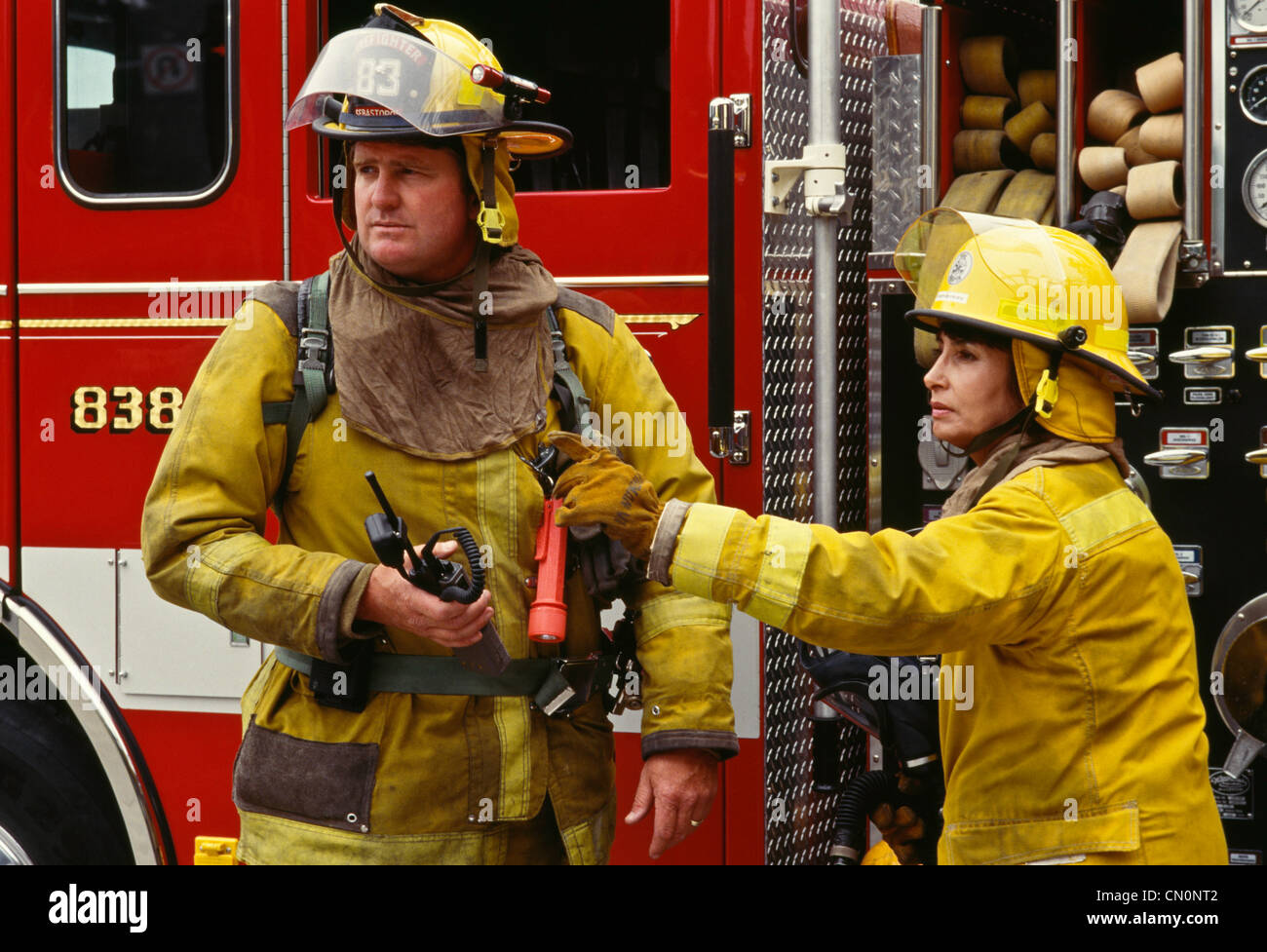 Male and female firefighters in full turnouts in front of ...