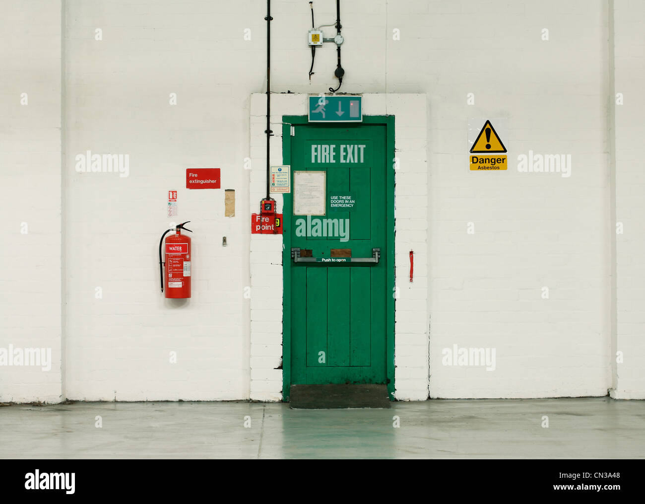 Fire exit door and signs in industrial building - Stock Image