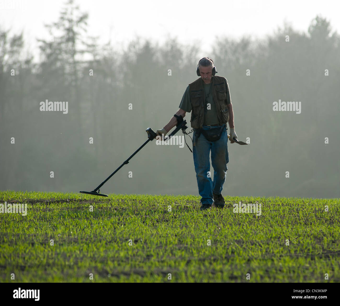 Jew Detector: A Man Searches In A Green Field Using A Metal Detector In