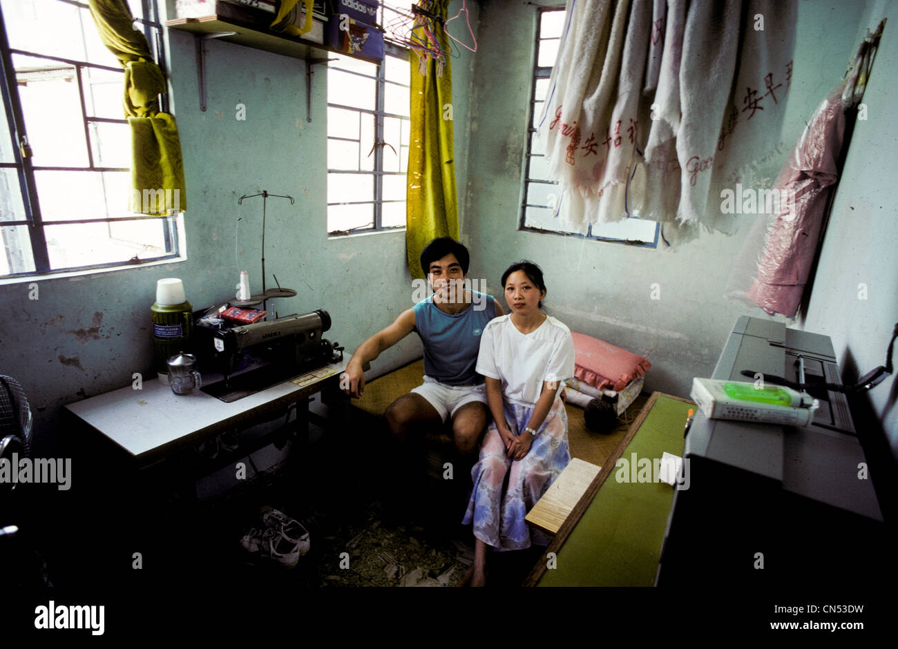 Young married couple sit in their one room studio apartment in ...