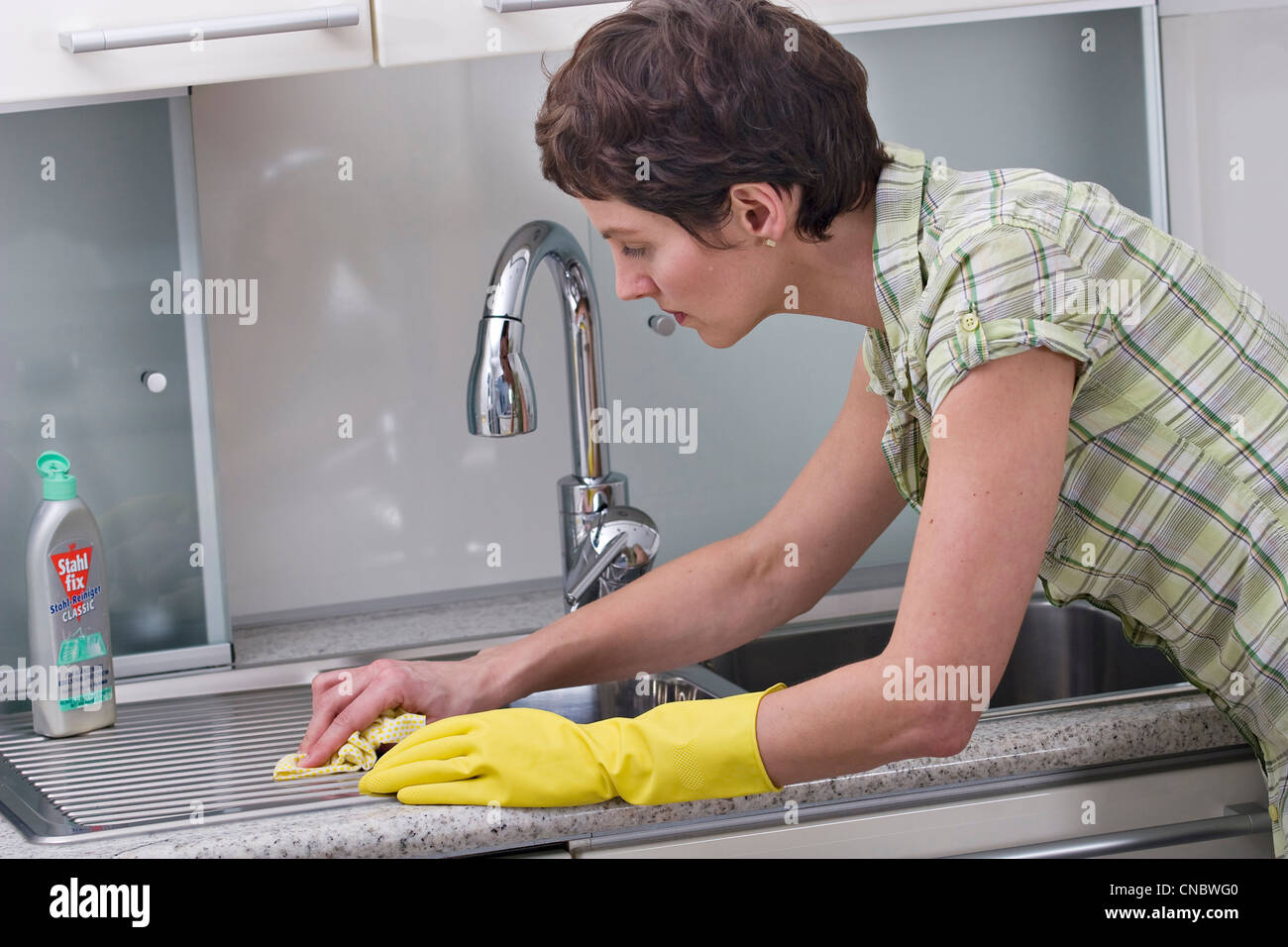 Woman cleaning kitchen sink Stock Photo, Royalty Free ...
