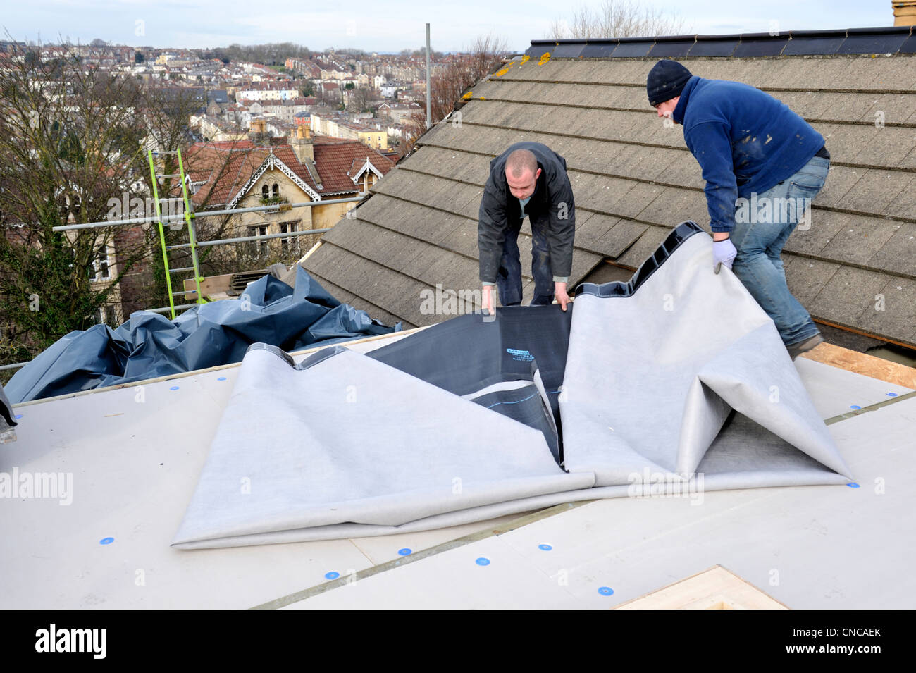 Roofers fitting flat roof with new epdm rubber membrane on house on stock photo royalty free - Advantages using epdm roofing membrane ...
