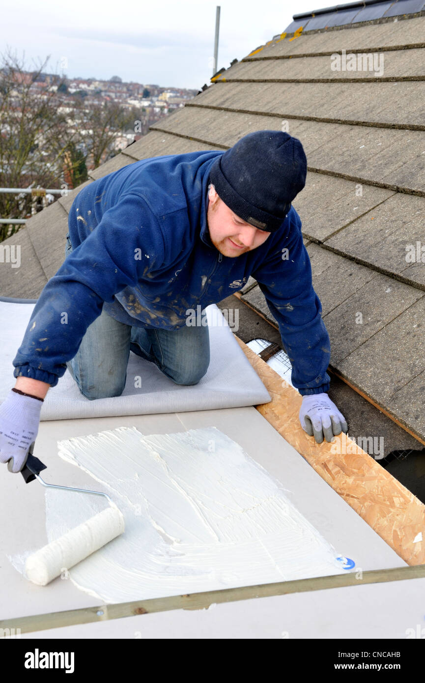 Roofer Spreading Adhesive On Insulation Board Of Flat Roof To Lay New EPDM  Rubber Membrane On House