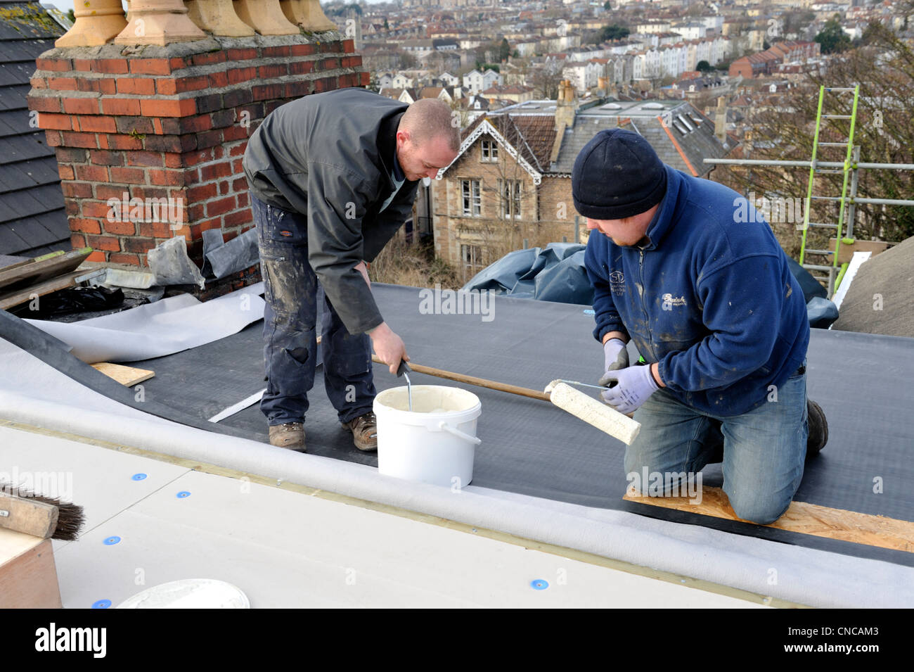 Roofers Spreading Adhesive On Insulation Board Of Flat Roof To Lay New EPDM  Rubber Membrane On House