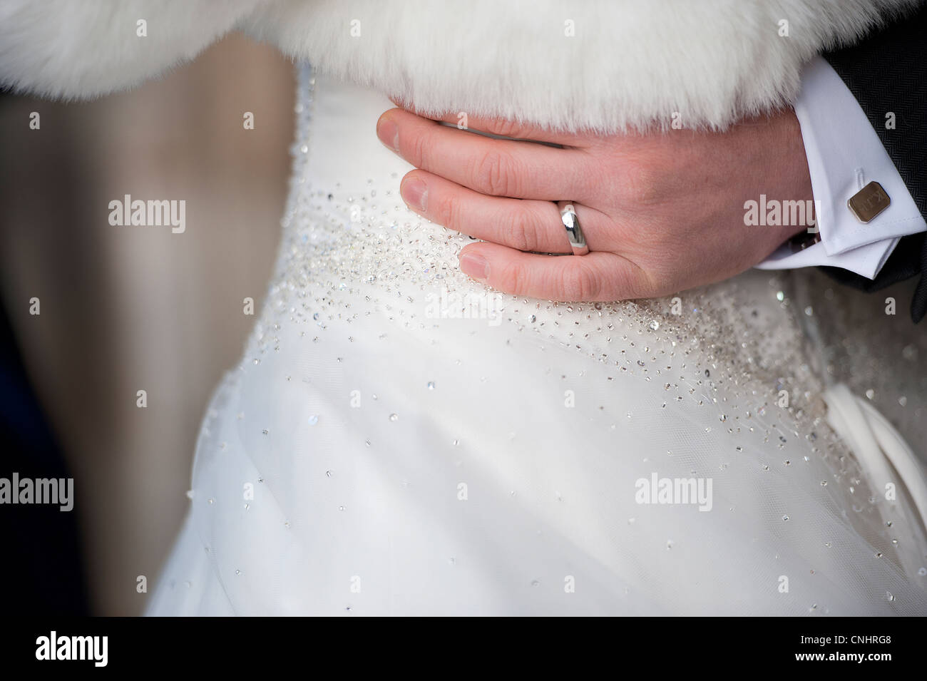 closeup of groom wearing wedding ring with his hand around brides