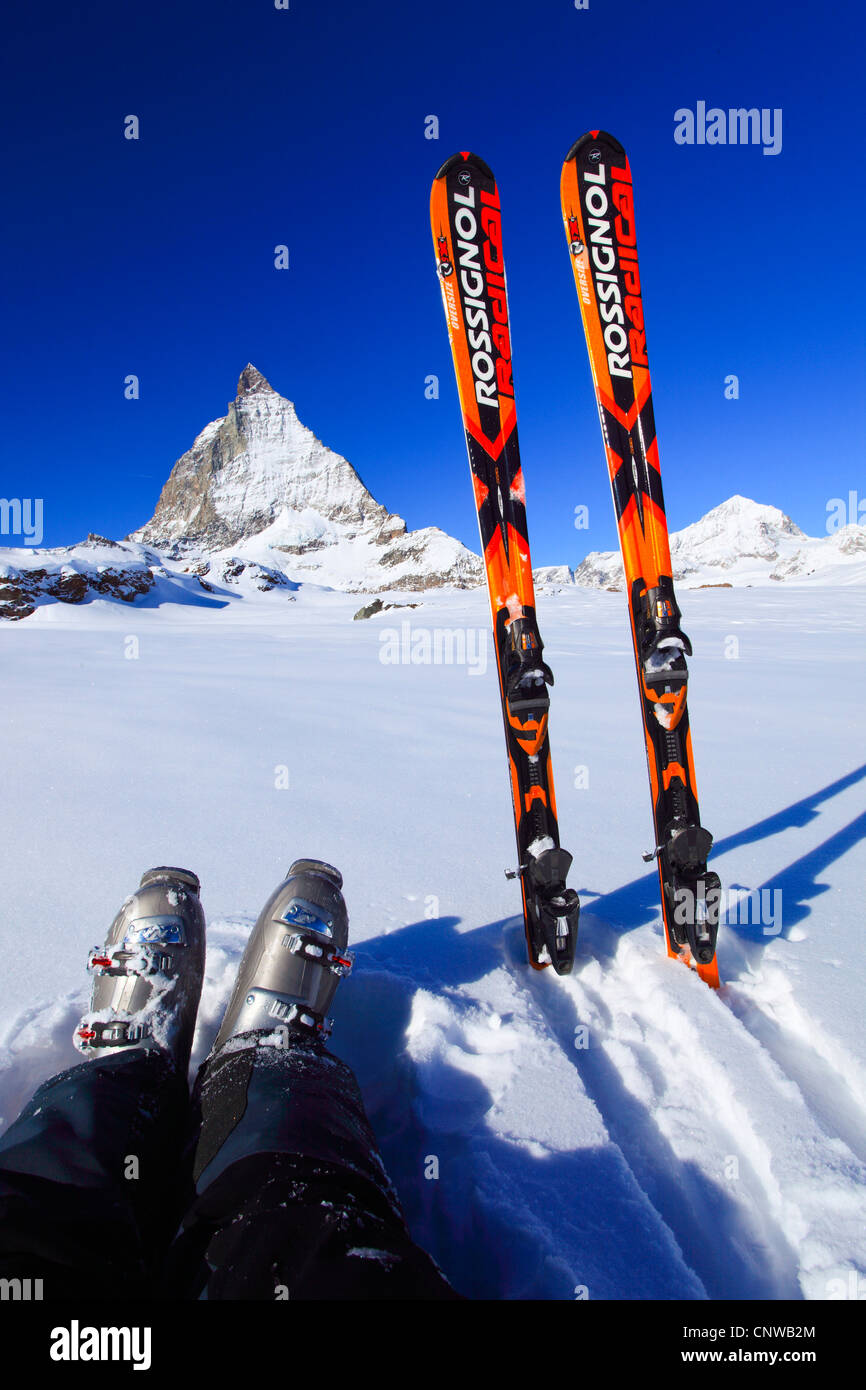 feet with hiking boots and skis in front of matterhorn