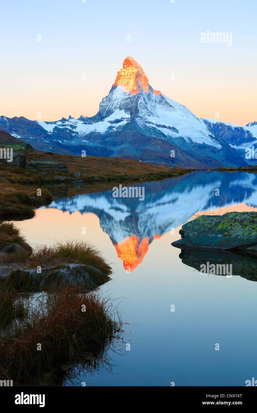 view from a mountain lake at the matterhorn with the top in golden