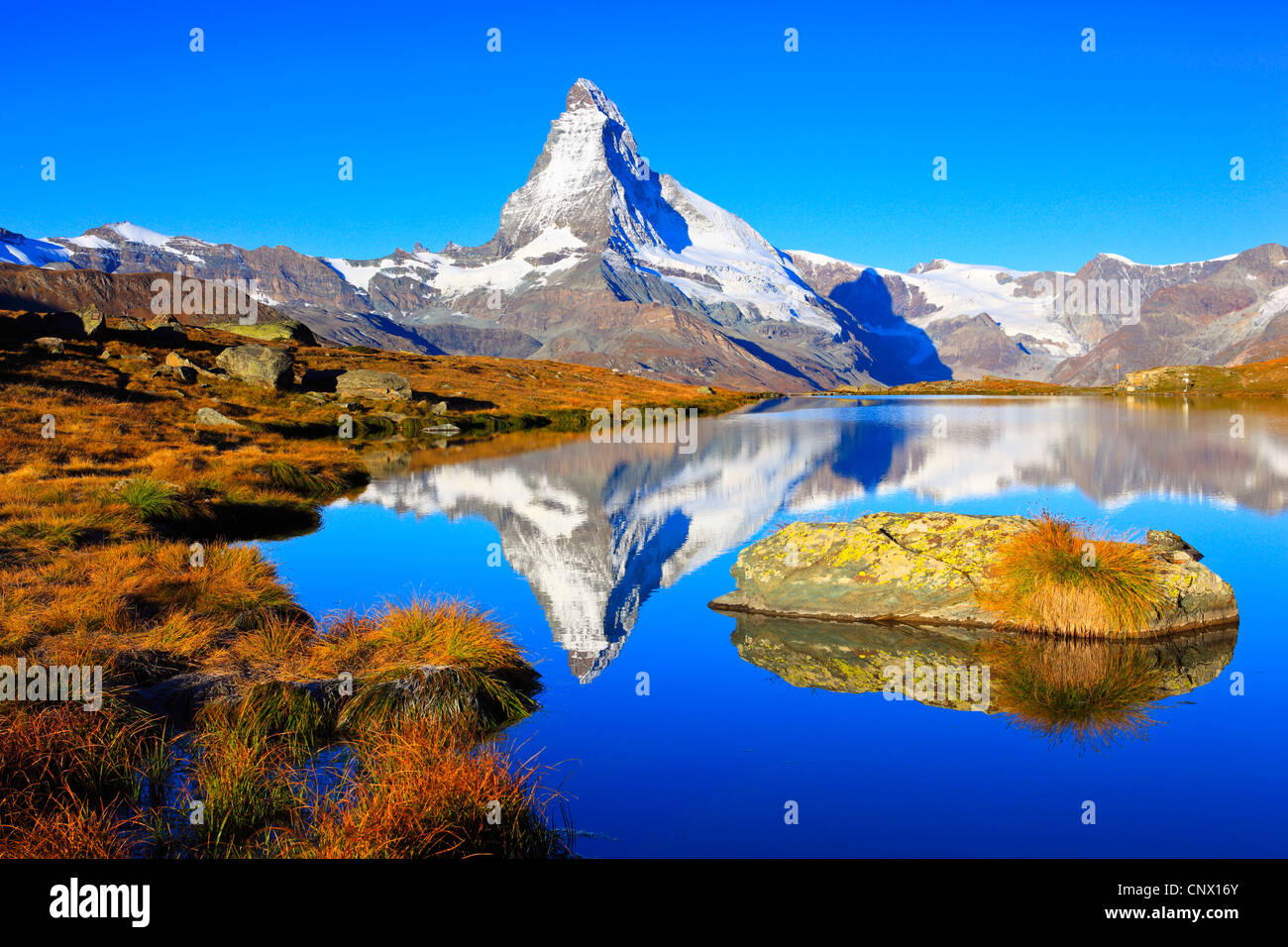 view from a mountain lake at the matterhorn under clear blue sky