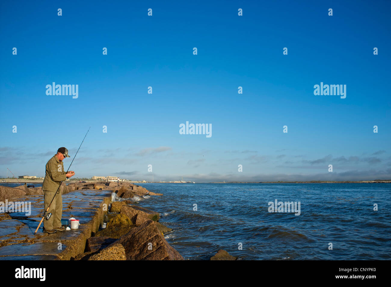 Man fishing off the jetties in port aransas at the gulf of for Port aransas jetty fishing report