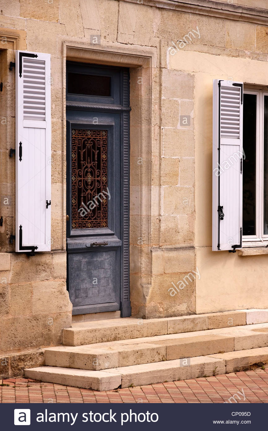Old blue wooden front door with ornate metal screen in stone house ...