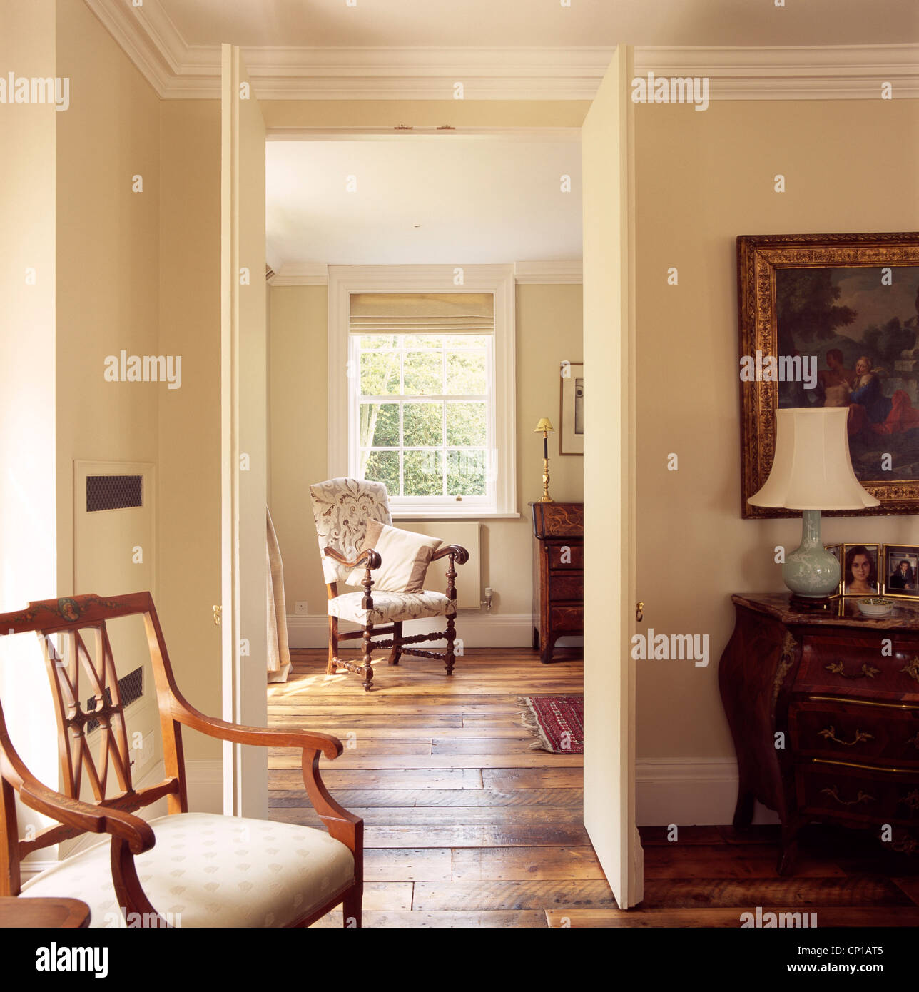 view through open door of traditional drawing room interior, uk