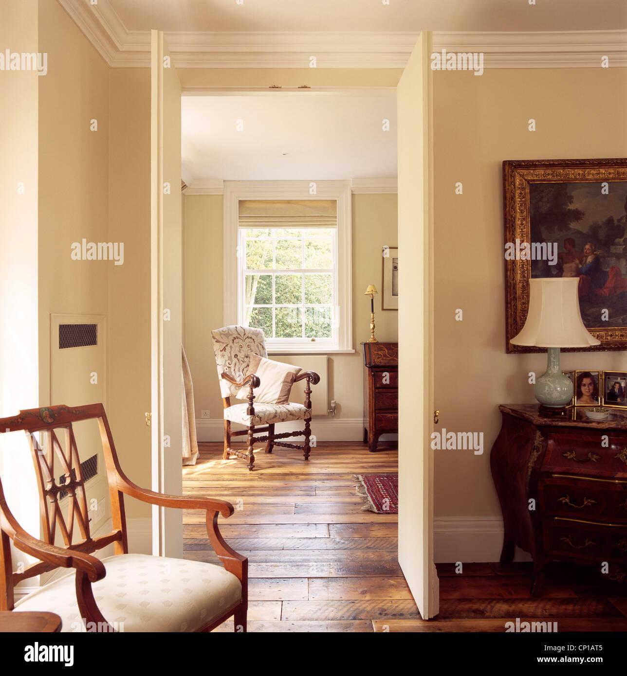 view through open door of traditional drawing room interior, uk
