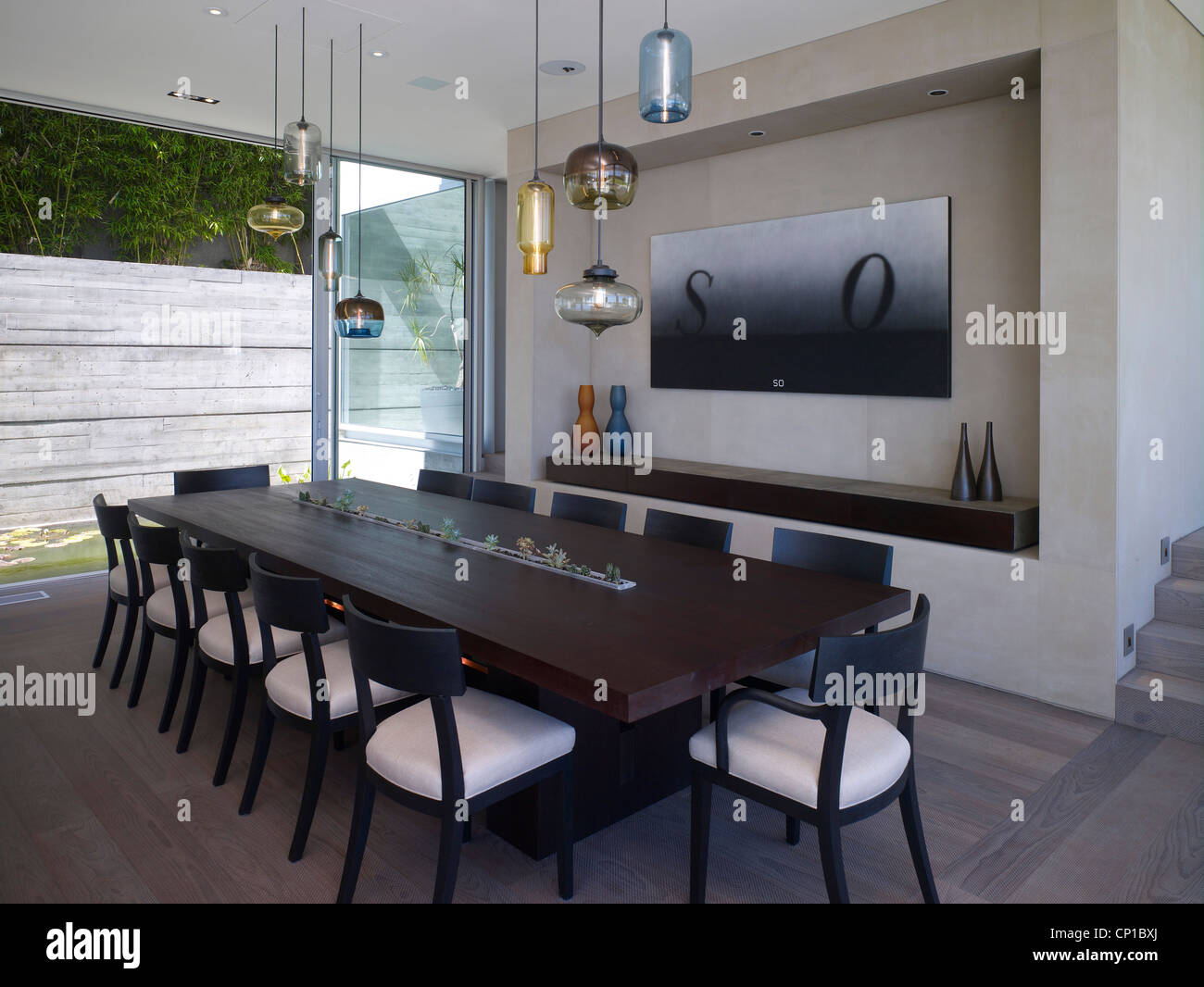 Dark wood dining table with assorted glass pendant lights in detached West  Hollywood home  California  USA. Dark wood dining table with assorted glass pendant lights in