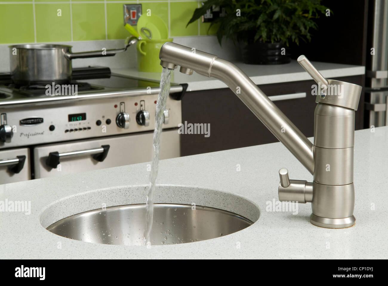 stock photo water running from tap into round sink set in worktop in modern kitchen. Interior Design Ideas. Home Design Ideas